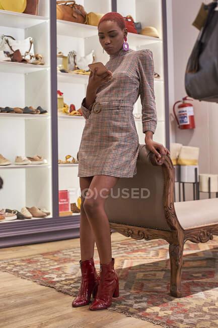 Mulher com um corte de cabelo colorido verificando relaxou seu telefone em uma loja de roupas — Fotografia de Stock