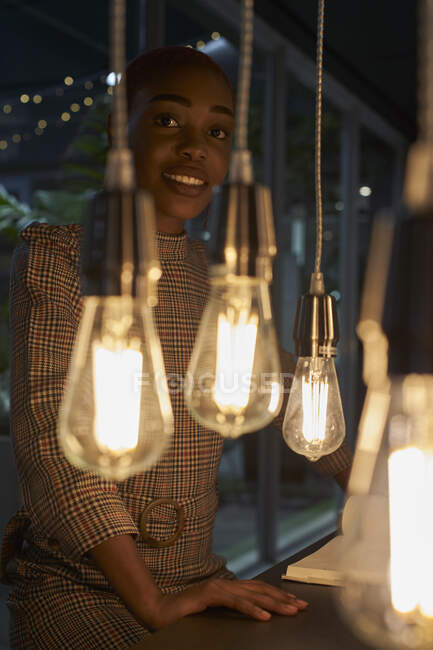 Mujer joven con el pelo corto detrás de las luces - foto de stock