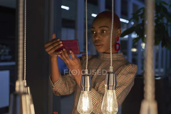 Mujer joven con corte de pelo corto revisando su maquillaje en su teléfono - foto de stock