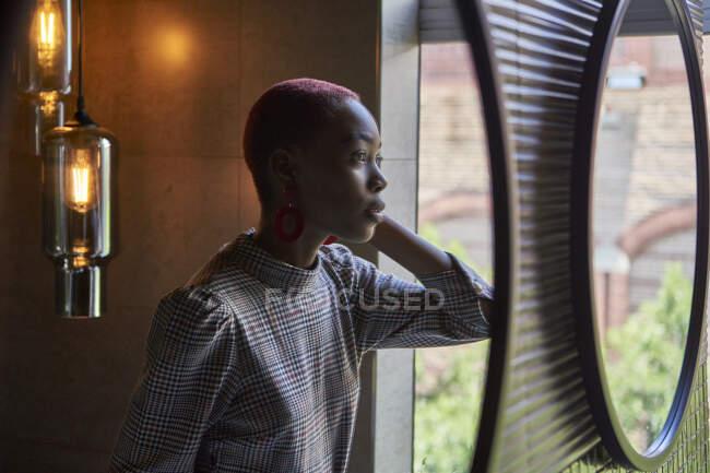 Mujer joven con corte de pelo corto mirando a su reflejo - foto de stock