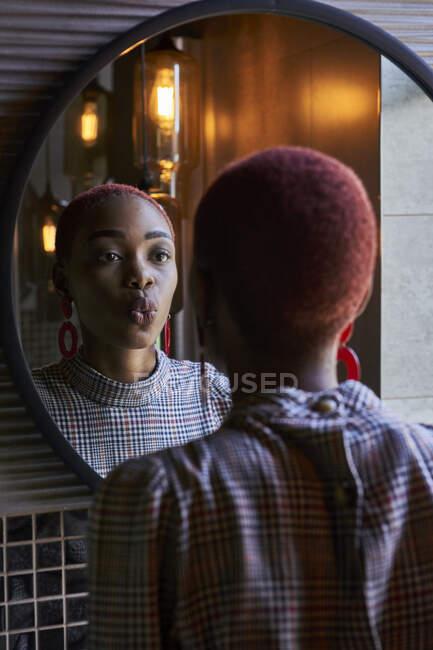 Mujer joven con corte de pelo corto mirando a su reflejo y enviando un beso en un espejo redondo - foto de stock