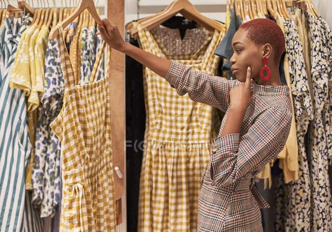 Жінка вибирає новий одяг, щоб купити в магазині. — стокове фото