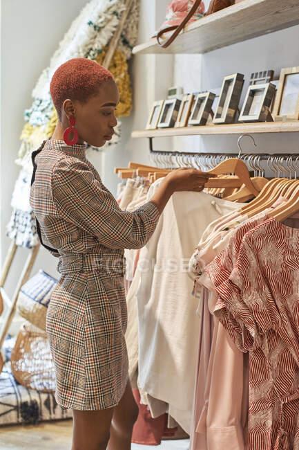 Mulher escolhendo roupas novas para comprar em uma loja — Fotografia de Stock