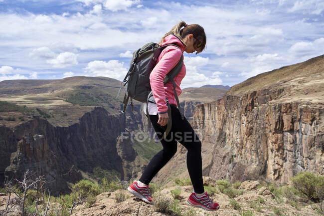 Женщина, идущая на вершину холма у водопада Малецуньяне, Лесото — стоковое фото