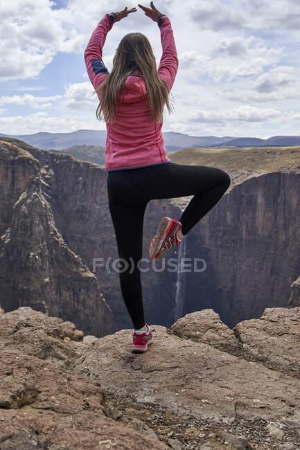 Mulher balançando no topo de uma colina em Maletsunyane Falls apreciando a vista, Lesoto — Fotografia de Stock