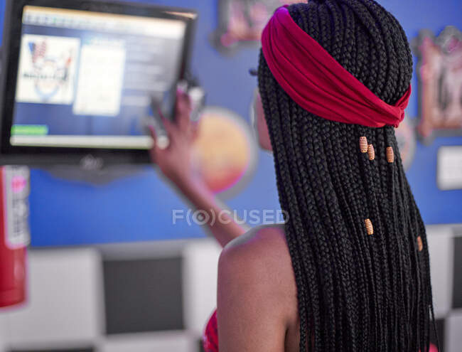 Young woman with braided hairstyle checking the orders on a screen — Stock Photo