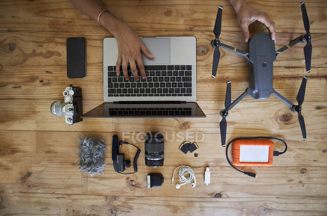 Person sitting at table with photografic equipment, using laptop, overhead view — Stock Photo