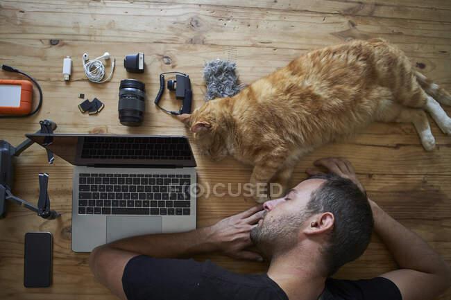 Виснажений чоловік спить на столі з імбирним котом, ноутбуком і фотографічним обладнанням. — стокове фото