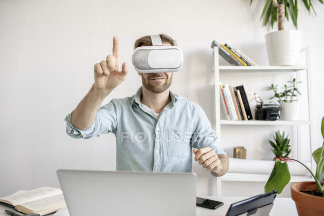 Man wearing VR glasses at desk in office — Stock Photo