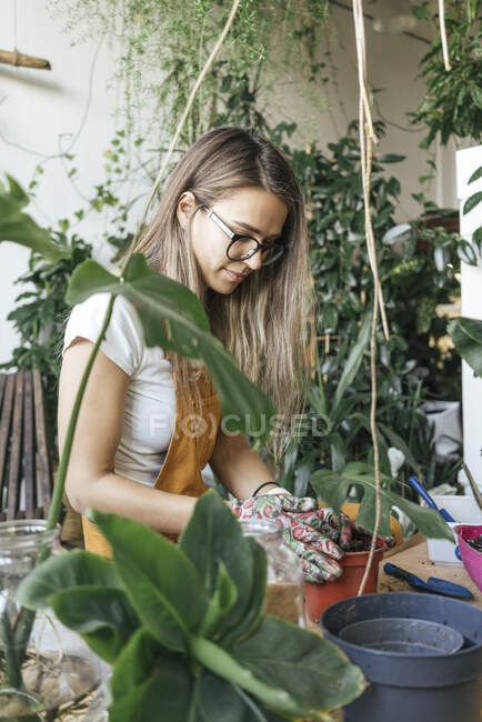 Young woman working with soil in a small gardening shop — Stock Photo