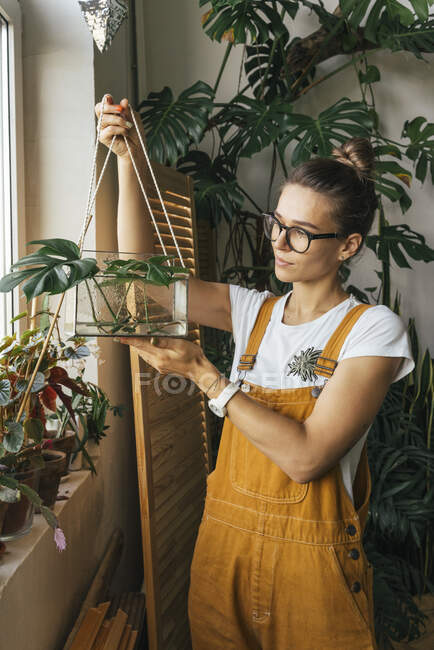 Young woman holding plant in a box with water — Stock Photo