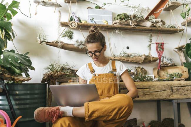 Молодая женщина использует ноутбук в небольшом садовом магазине — стоковое фото