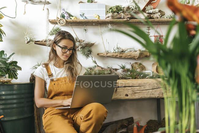 Jeune femme utilisant un ordinateur portable dans une petite boutique de jardinage — Photo de stock