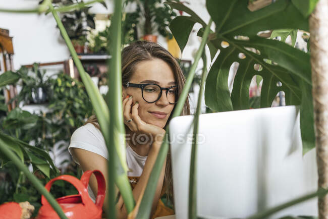 Young woman using laptop surrounded by plants — Stock Photo