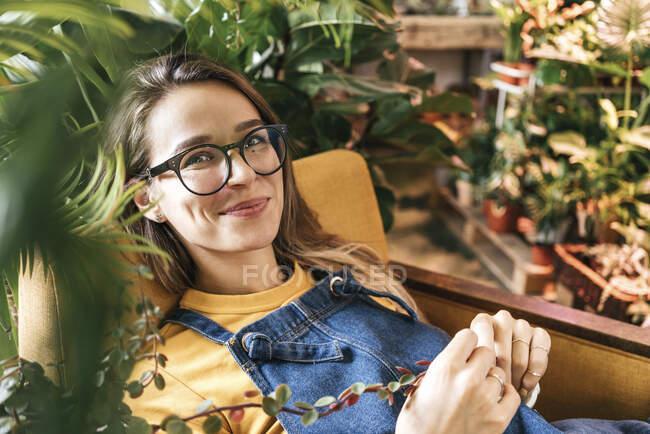 Портрет усміхненої молодої жінки, що сидить у кріслі в оточенні рослин. — стокове фото