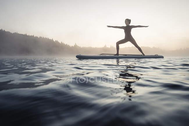 Donna che pratica paddle board yoga sul lago Kirchsee al mattino, Bad Toelz, Baviera, Germania — Foto stock