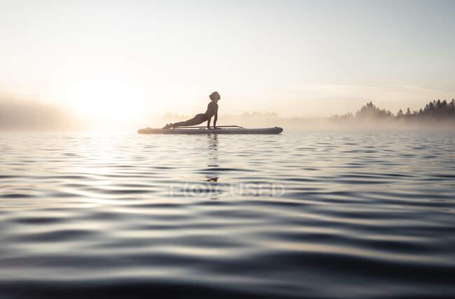 Женщина практикует гребную йогу на озере Кирхзее утром, Бад-Тоэльц, Бавария, Германия — стоковое фото