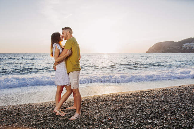 Young couple kissing at the beach during sunset — Stock Photo