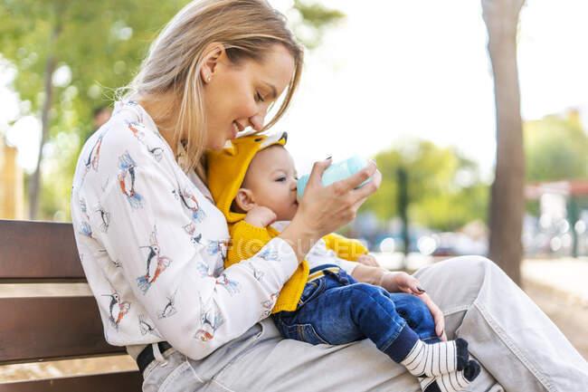 Мати годує маля пляшкою на лавці в парку. — стокове фото