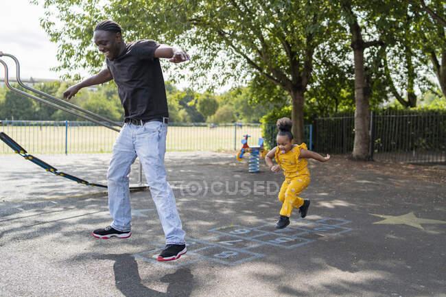 Батько з дочкою грають у хопскоч на ігровому майданчику. — стокове фото