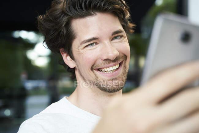 Портрет щасливого чоловіка, який тримає мобільний телефон у місті. — стокове фото