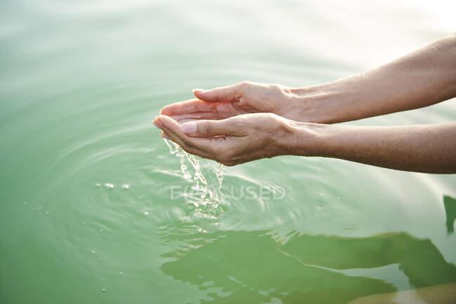 Primer plano de las manos de la mujer tocando el agua de un lago - foto de stock