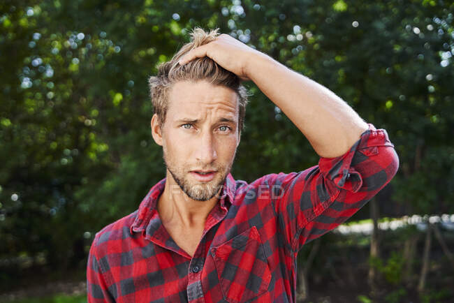 Portrait of young man wearing checkered shirt outdoors — Stock Photo