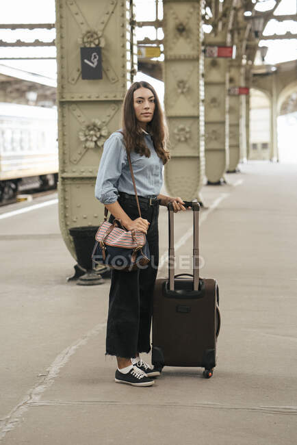 Young female traveller standing on train station — Stock Photo