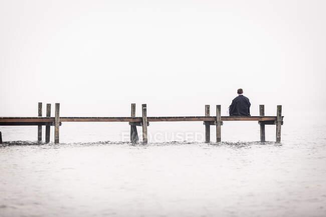 Vista posteriore dell'uomo seduto sul molo sul lago Starnberg, Germania — Foto stock