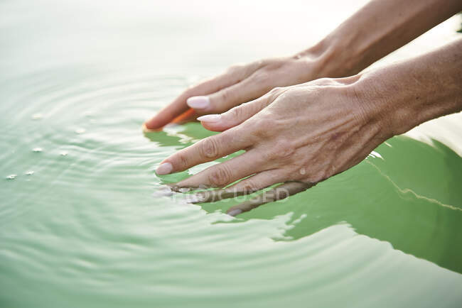 Close-up of woman's hands touching water of a lake — Stock Photo