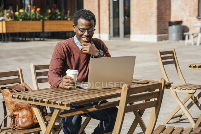 Young man using laptop in a coffee shop, drinking coffee — Stock Photo