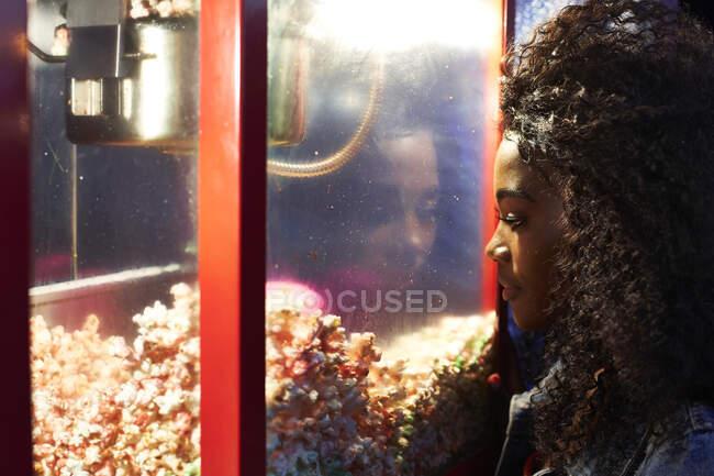 Mujer joven mirando palomitas de maíz en vitrina en feria - foto de stock