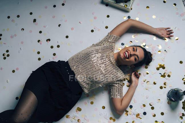Портрет молодої жінки, одягненої на вечірку, святкуючи Різдво подарунками й шампанським. — стокове фото