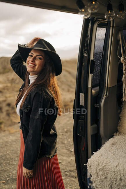 Portait de joven sonriente en paisaje desértico de pie junto a autocaravana, Almería, Andalucía, España - foto de stock