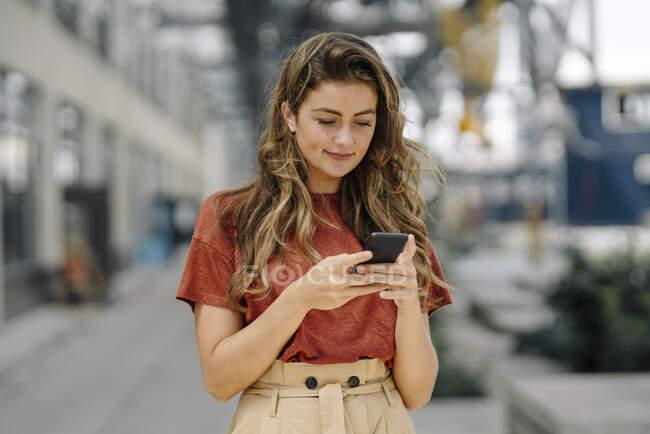 Retrato de una joven morena sonriente usando un smartphone, mirando hacia abajo - foto de stock