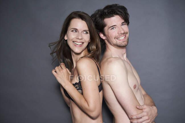 Портрет счастливой полуодетой пары спина к спине — стоковое фото
