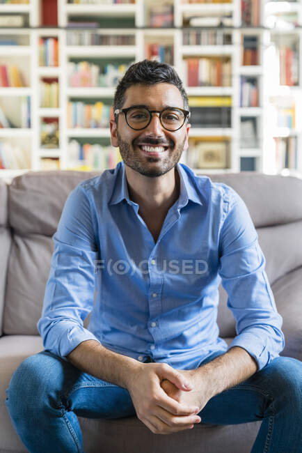 Portrait of happy young man sitting on the couch at home — Stock Photo