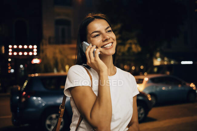 Молода жінка вночі користується смартфоном у місті. — стокове фото