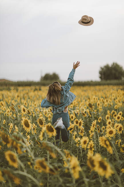 Rear View of young woman with blue denim jacket throwing a hat in a field of sunflowers — Stock Photo