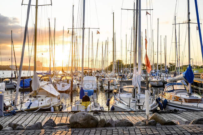 Germany, Schleswig-Holstein, Niendorf, Various boats moored in harbor at sunset — Stock Photo