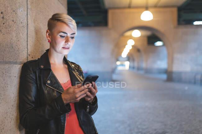 Retrato de mulher loira olhando para smartphone à noite, Berlim, Alemanha — Fotografia de Stock