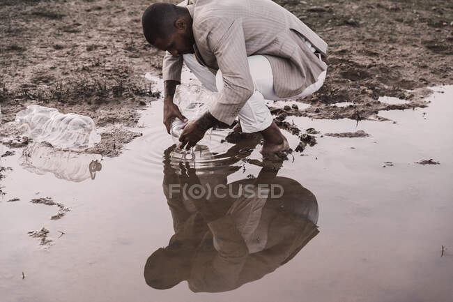 Joven hombre llenando botella de plástico con agua en un agujero de agua - foto de stock