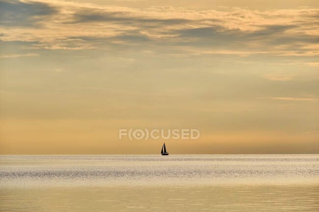 Italy, Trentino, Nago-Torbole, Silhouette of sailboat sailing across Lake Garda at moody dawn — Stock Photo