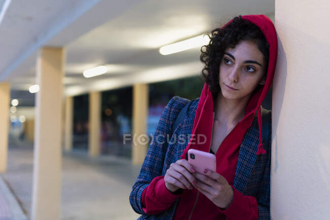 Portrait of young woman with mobile phone in the evening — Stock Photo