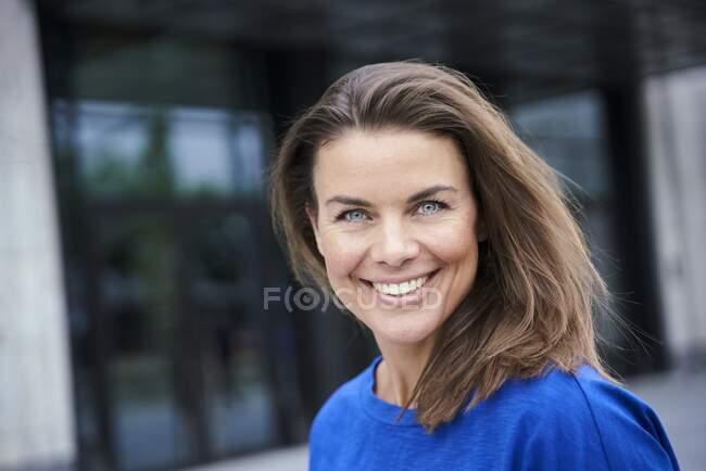 Porträt einer attraktiven brünetten Frau mit blauem Top in der Stadt — Stockfoto