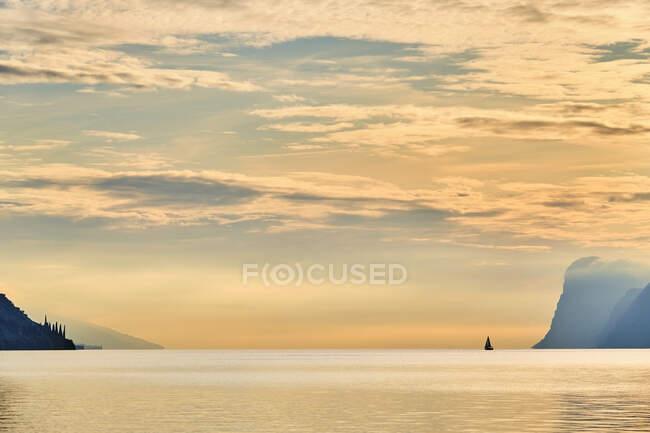 Italy, Trentino, Nago-Torbole, Silhouette of sailboat sailing near coastal cliffs of Lake Garda at moody dawn — Stock Photo