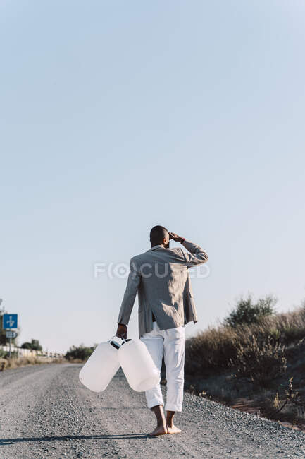 Young man holding empty water cans walking on dirt track — Stock Photo
