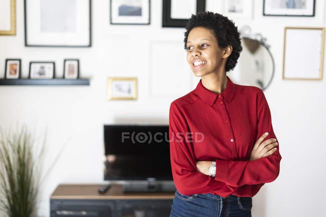 Sorridente giovane donna a casa guardando lateralmente — Foto stock