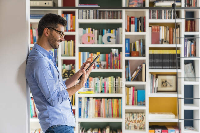 Smiling young man standing in front of bookshelves at home using digital tablet — Stock Photo