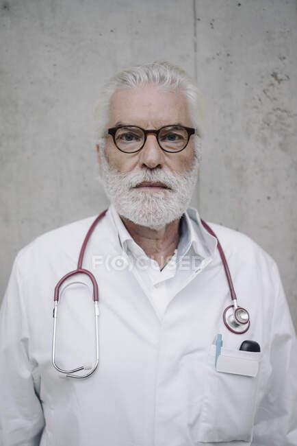 Retrato de un médico serio en una pared de hormigón - foto de stock